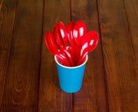 Устранимая ложка бумажного стаканчика и пластмассы на древесине темноты предпосылки Стоковое фото RF