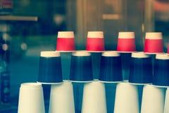 Устранимые бумажные стаканчики в витрине кафа кофе идет к Красный цвет, черно-белые экологические чашки различных размеров и форм Стоковая Фотография
