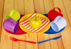 Устранимые плиты, пластичные чашки, нож, вилка, яблоко на светлой древесине Стоковые Фото