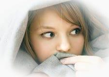Устрашенная девушка лежа под одеялом стоковое изображение rf