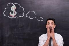 Устрашенный бизнесмен при знак доллара покрашенный дальше Стоковое Изображение RF