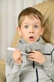 Устрашенный мальчик с термометром в его руках смотря наивный Стоковое Изображение