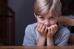 Устрашенный ребенк сидя на таблице Стоковое Фото