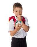 Устрашенный школьник с будильником в руке Стоковые Изображения RF