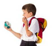 Устрашенный школьник с будильником в руке Стоковые Фото