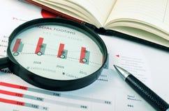 Устроитель, ручка, лупа над диаграммой стоковые изображения