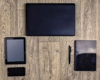 Устройства на деревянной предпосылке, взгляд сверху, компьтер-книжке, smartphone, таблетке, ручке Стоковое Фото