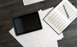 Устройства на деревянном столе Документы таблетки компьютера Стоковое фото RF