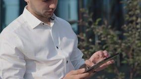 Устройство в руках молодого бизнесмена Он новости чтения, проверяя электронную почту сток-видео