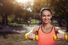 Услаженная девушка держа гантели на ее тренировке outdoors Стоковые Изображения