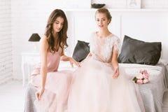 Услаженная невеста и bridesmaid сидя в белой комнате Стоковое Фото