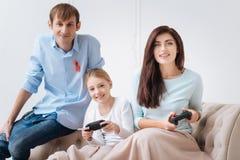 Услаженная положительные мать и дочь играя видеоигры Стоковые Изображения