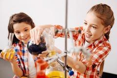 Услаженные милые девушки наслаждаясь их уроком химии Стоковая Фотография RF
