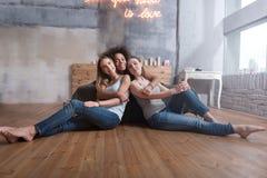 Услаженные друзья обнимая в спальне дома Стоковая Фотография
