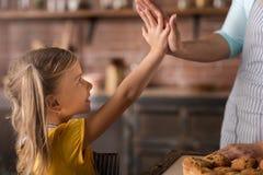 Услаженные руки девушки касающие ее матери в кухне Стоковое Фото