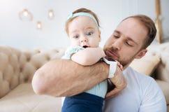 Услаженный молодой отец забавляя его дочь дома Стоковые Фото