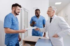 Услаженный старея доктор проверяя качество работы в клинике Стоковое Изображение