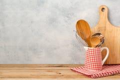 Утвари и разделочная доска кухни на деревянном столе над деревенской предпосылкой стоковое изображение rf