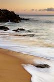 Утесистый пляж на заходе солнца Стоковые Изображения RF
