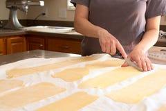 Утеска шеф-повара свернула тесто макаронных изделий в кухне Стоковое фото RF