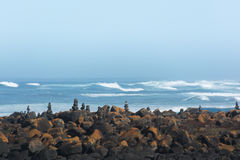Утесы балансируя в стоге на каменном покрытом пляже с океаном позади Стоковое Изображение RF