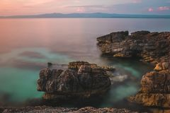 Утесы в море на заходе солнца стоковые фото