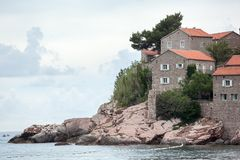 Утесы на береге и каменных домах острова и гостиницы Sveti Stefan Балканы, Адриатическое море, Черногория, Европа стоковое изображение