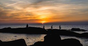 Утесы на море встают на сторону с небом захода солнца темы силуэта стоковая фотография rf