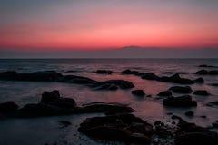 Утесы на море встают на сторону с темой силуэта в вечере стоковое изображение