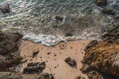 Утесы на пляже с солнечным светом стоковые изображения