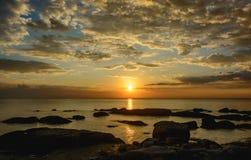 Утесы на пляже с небом захода солнца стоковое изображение rf