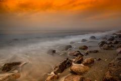 Утесы под оранжевым заходом солнца Стоковое фото RF
