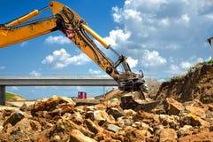 Утесы работника moving с землечерпалкой на строительной площадке Стоковая Фотография