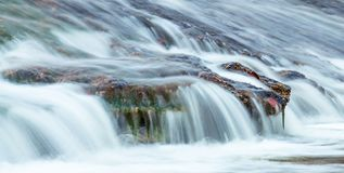 Утесы реки под брызгать воду стоковые изображения rf