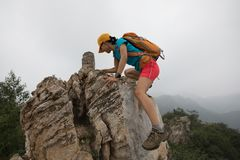 утес альпиниста женщины взбираясь на верхней части горы Стоковое Фото