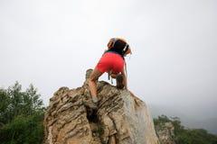 утес альпиниста женщины взбираясь на верхней части горы Стоковые Изображения