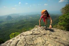 утес альпиниста женщины взбираясь на верхней части горы Стоковые Фото