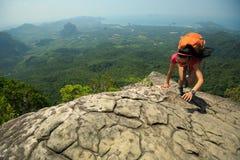 утес альпиниста женщины взбираясь на верхней части горы Стоковое Изображение RF