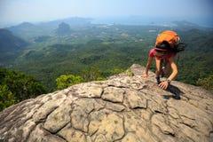 утес альпиниста женщины взбираясь на верхней части горы Стоковая Фотография RF
