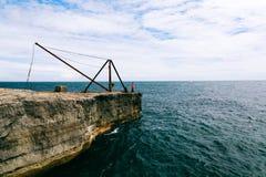 Утес и ржавый стальной кран ` s рыболова около Портленда представляют счет маяк Стоковое фото RF