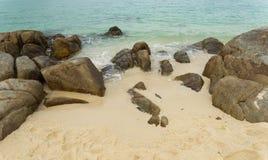 Утес на пляже с белым песком с зеленым океаном Стоковое Изображение RF