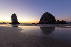 Утес стога сена на пляже карамболя после захода солнца Стоковые Фотографии RF