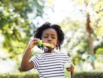Утеха девушки отдыха ребенк пузыря дуя вскользь Стоковые Изображения
