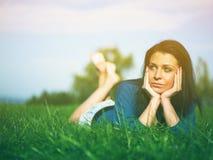 Утеха молодой женщины и ослаблять на траве Стоковые Изображения