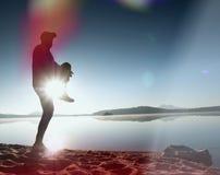 Утечка света в объективе Идущий человек Бег спортсмена, jogging парень во время восхода солнца над песчаным пляжем Стоковое Изображение