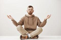 Утихомиривать вниз и соединять с природой Уверенно расслабленный молодой буддист в стильных одеждах сидя в городском парке с стоковые фото