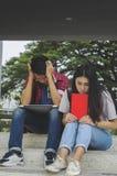 Утомленная группа студентов при книги сидя на поле Пробуренный, автошина Стоковое фото RF