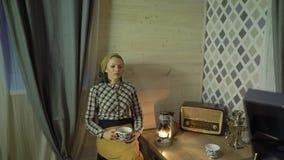 Утомленная девушка портноя имеет остатки, чай пить, ослабляет, слушает музыка на плите, патефоне или фонографе винила ретро сток-видео