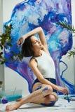 Утомленная девушка представляя на предпосылке вычерченного изображения с paintbrush Стоковые Изображения