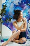 Утомленная девушка представляя на предпосылке вычерченного изображения с paintbrush Стоковое Изображение RF